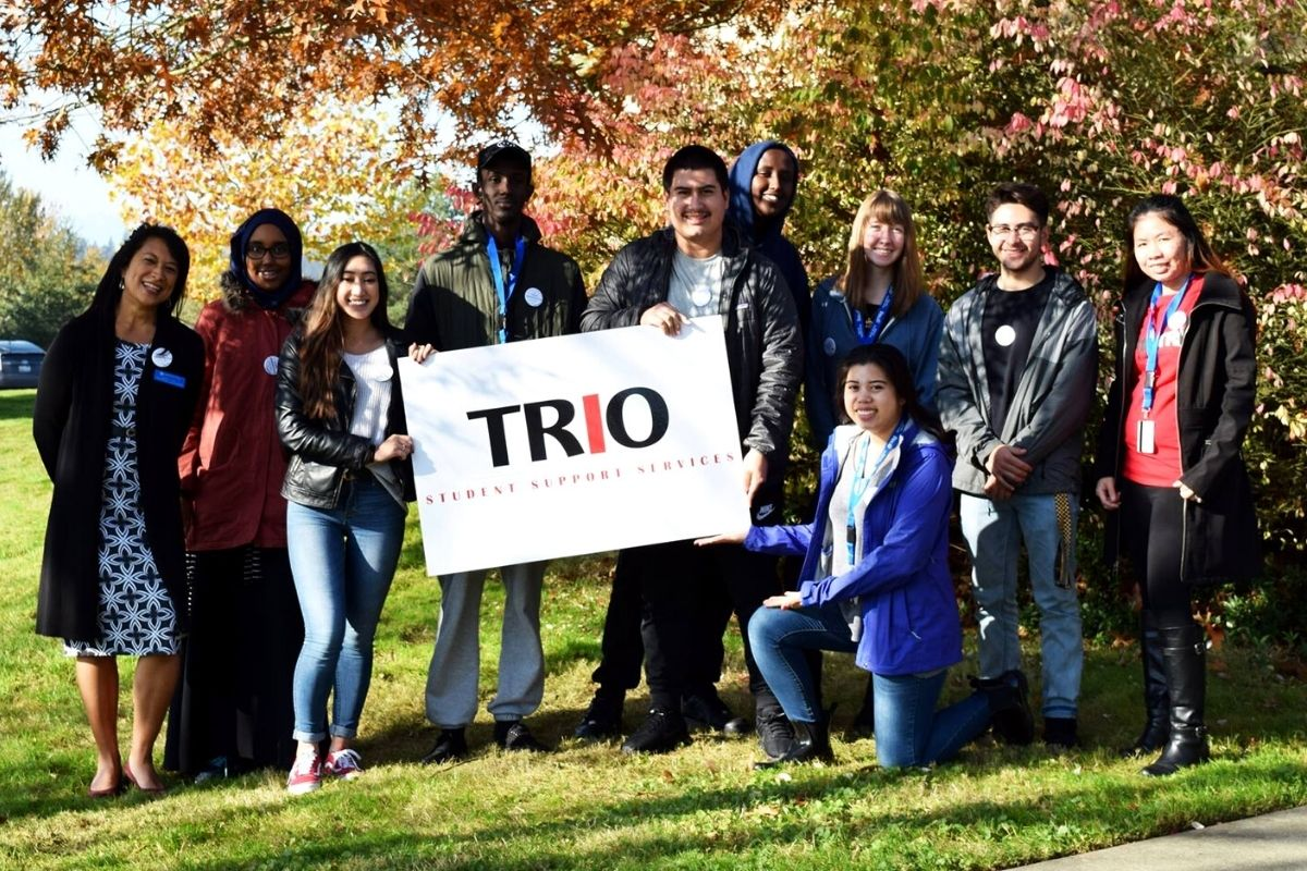 TRIO students posing surrounded by autumn foliage